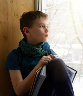 Garçon assis près de la fenêtre avec un livre et regardant le jour d'hiver, à l'intérieur. un adolescent regarde par la fenêtre.