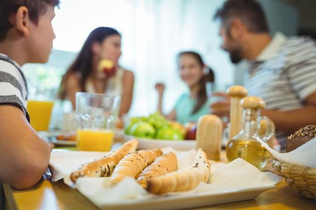 Garçon assis à table avec un plateau de pain français devant