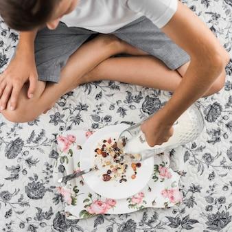 Un garçon assis sur un tapis floral, versant du lait dans les flocons d'avoine