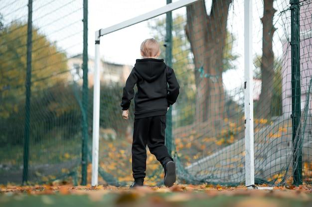 Un garçon d'athlète se tient devant le but et attend que le ballon serve.