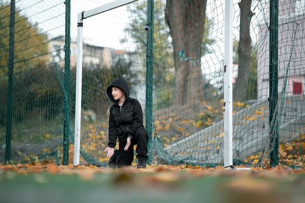 Garçon - athlète se tient à la porte du terrain de football en automne.