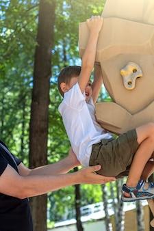 Garçon athlétique pratiquant l'escalade sur mur d'escalade sur aire de jeux. parc d'attractions pour enfants