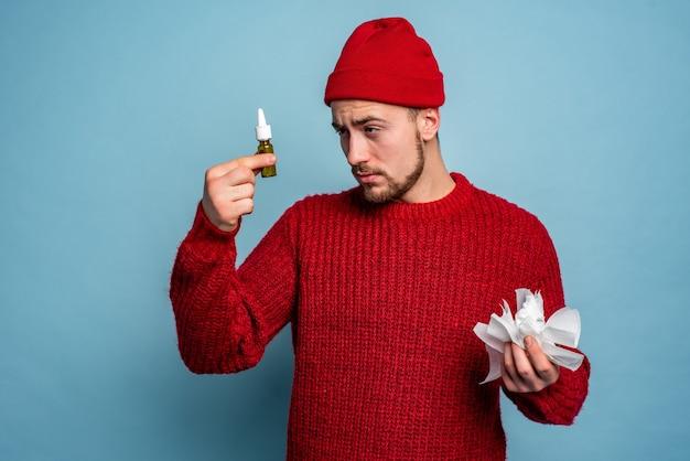 Un garçon a attrapé un rhume et utilise un spray pour guérir