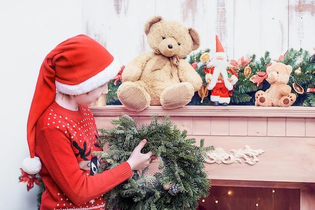 Garçon au bonnet de noel décorer le salon et la cheminée pour noël ou le nouvel an.