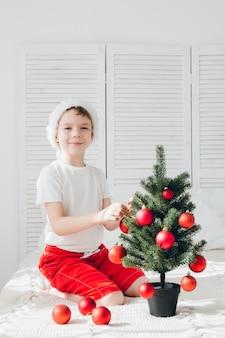 Garçon au bonnet rouge décore une petite boules de sapin
