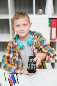 Garçon au bureau avec télécommande