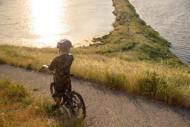 Garçon au casque sur son vélo de montagne au coucher du soleil