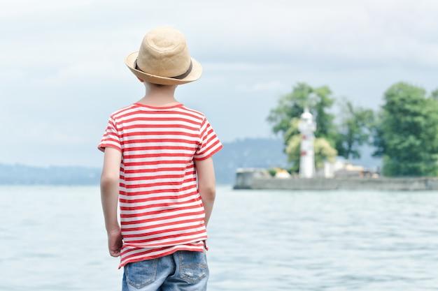 Garçon au chapeau, debout sur la plage. petit phare au loin. vue arrière