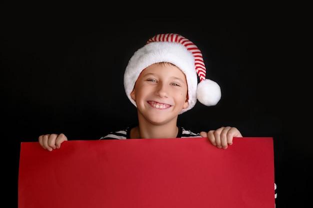 Garçon au chapeau du père noël tenant l'affiche vierge rouge pour les voeux de noël. isolé sur noir