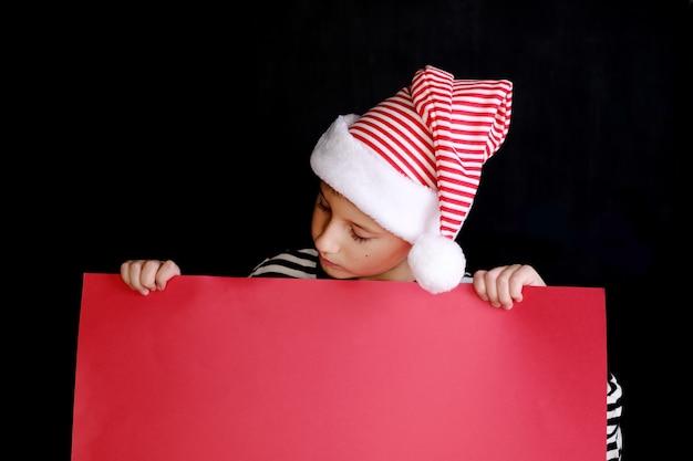 Garçon au chapeau du père noël tenant le papier blanc rouge pour les voeux de noël. isolé sur noir
