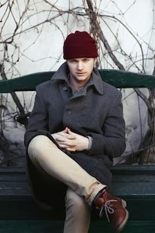 Garçon au chapeau rouge est assis sur le banc vert
