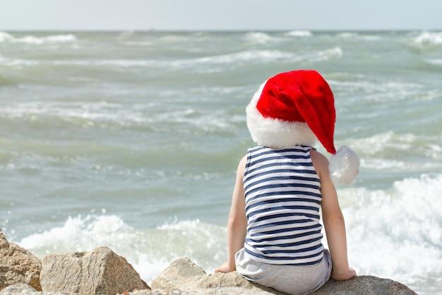 Garçon au chapeau et t-shirt rayé du père noël est assis sur la plage