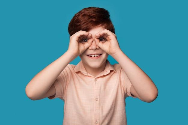 Garçon au gingembre fait des gestes comme avoir des jumelles sur les yeux