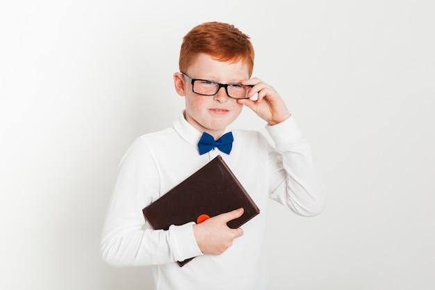Garçon au gingembre avec lunettes et livre