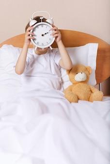 Garçon au lit avec grand réveil