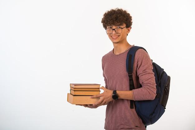 Garçon aux cheveux bouclés dans des lunettes optiques tenant des livres scolaires à deux mains et souriant.