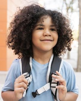 Garçon aux cheveux bouclés de nouveau à l'école, préscolaire, saisissant son sac à dos heureux souriant