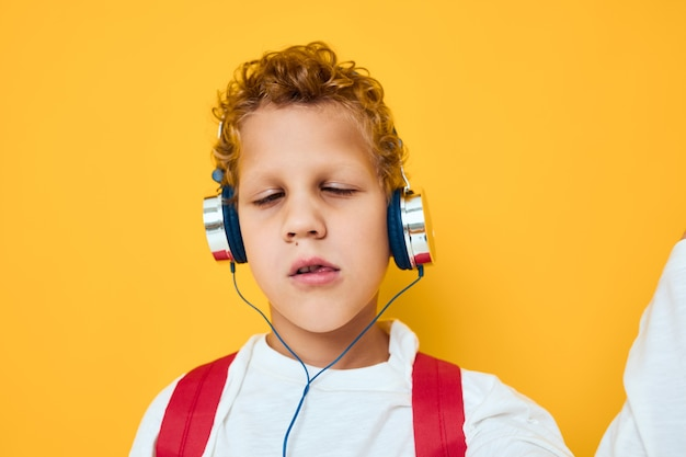 Garçon aux cheveux bouclés portant des écouteurs écoutant de la musique