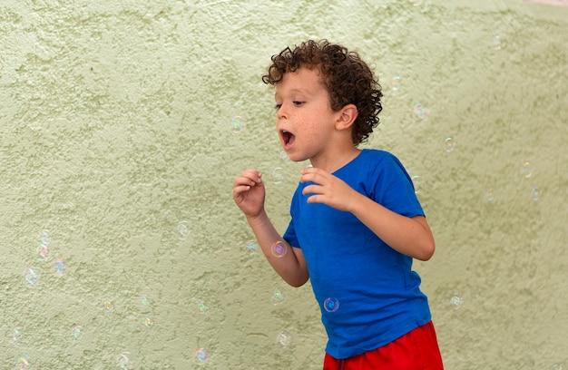 Garçon aux cheveux bouclés avec des taches de rousseur jouant dans la cour avec des bulles de savon.