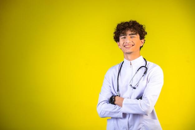 Garçon aux cheveux bouclés en uniforme médical blanc avec stéthoscope.
