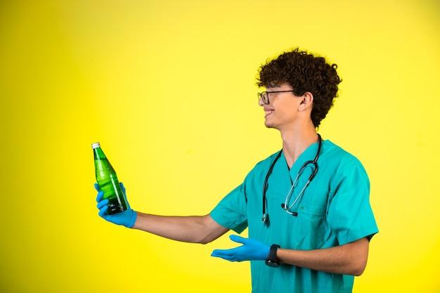 Garçon aux cheveux bouclés en uniforme médical et masques à la main à la recherche d'une bouteille de liquide et souriant.