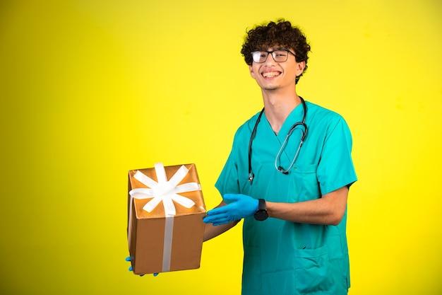 Garçon aux cheveux bouclés en uniforme médical et masques à main tenant une boîte-cadeau.