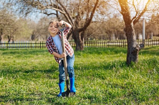 Garçon aux cheveux brun radiant portant des bottes de wellington bleu riche avec pied sur une pelle à l'avant et souriant
