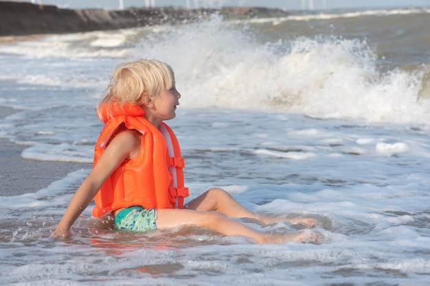 Garçon aux cheveux clairs dans un gilet gonflable orange assis sur le bord de la mer et en attente de grosse vague.