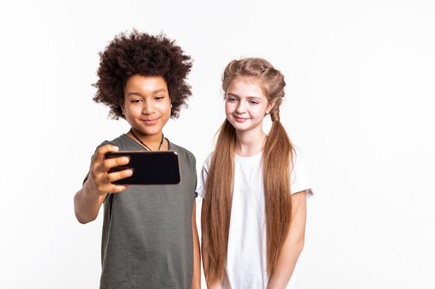 Garçon aux cheveux noirs. de jolis jeunes enfants faisant du selfie ensemble sur un smartphone tout en se tenant étroitement en studio