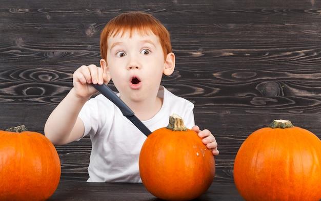 Un garçon aux cheveux rouges coupés avec un couteau à citrouille lors de la préparation d'un repas ou pour l'halloween