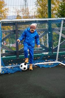 Garçon avec le ballon près du but de football. concept de sports de plein air
