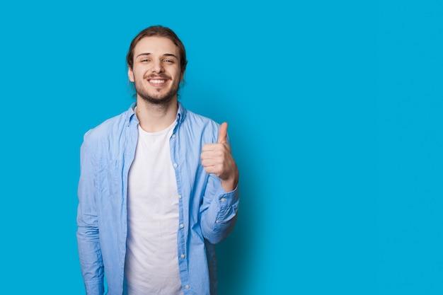 Garçon barbu faisant des gestes le signe comme regardant avec confiance la caméra sur un mur bleu avec de l'espace libre