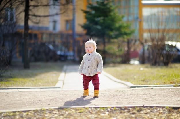 Garçon beau bambin marchant en plein air au printemps chaud