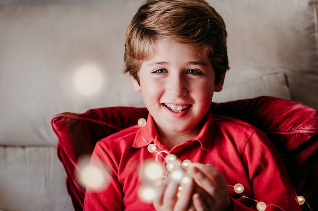 Garçon beau gosse à la maison jouant avec guirlande de lumières