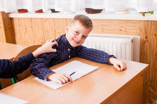 Garçon blanc dans le cahier pendant la leçon de l'école primaire. deux garçons parlent et n'écoutent pas le professeur