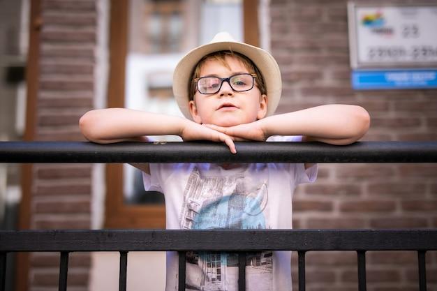 Garçon blond au chapeau de paille et grands verres logés parmi de belles vieilles maisons