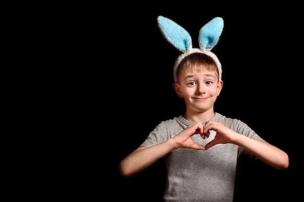 Garçon blond aux oreilles de lièvre a croisé ses mains en forme de coeur sur sa poitrine sur fond noir