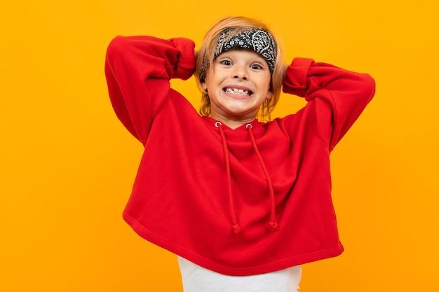 Garçon blond avec un bandana sur la tête dans une veste rouge