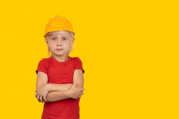 Garçon blond en casque de protection sur fond jaune. choix du futur métier.