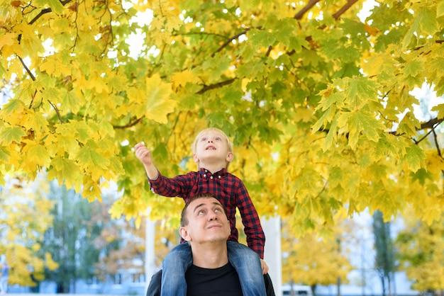 Un garçon blond en chemise à carreaux est assis sur les épaules de son père. chercher. concept d'automne
