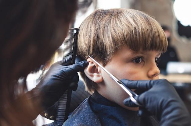Garçon blond coiffé dans un salon de coiffure par une coiffeuse.