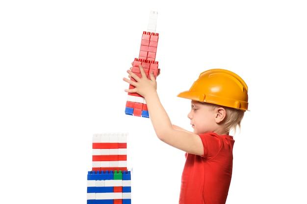 Un garçon blond dans un casque de construction construit un gratte-ciel à partir des détails du concepteur.