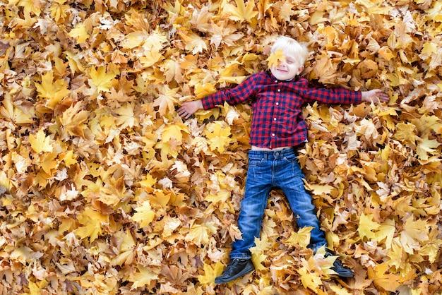 Garçon blond dans une chemise à carreaux se trouve dans les feuilles d'automne jaunes. vue de dessus. concept d'automne