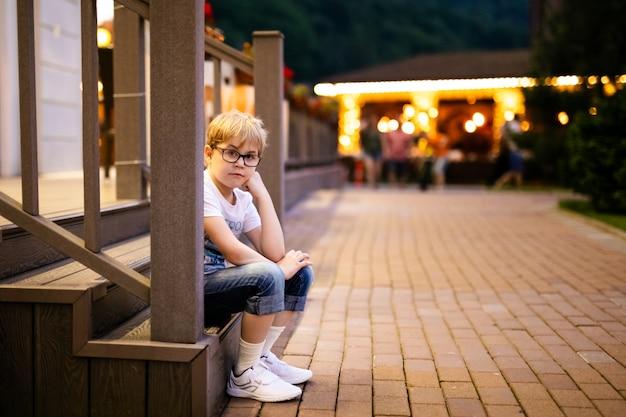 Garçon blond dans les grandes lunettes marchant dehors le soir