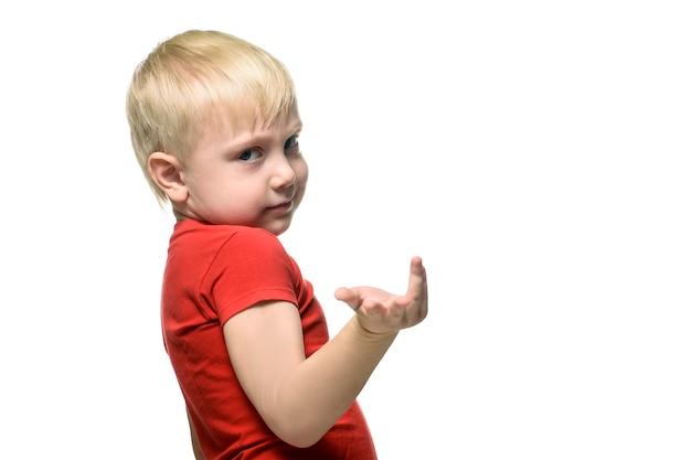 Garçon blond dans un t-shirt rouge se tient un demi-tour et montre un geste de la main. isoler sur fond blanc.