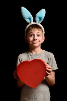 Un garçon blond drôle dans les oreilles de lièvre détient une boîte en forme de coeur rouge sur fond noir