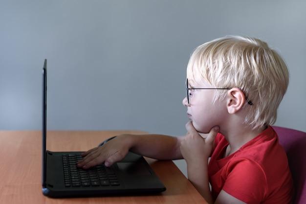 Garçon blond drôle dans des verres est assis devant un ordinateur portable. internet et préscolaire