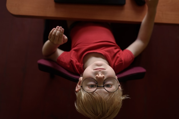 Garçon blond drôle dans des verres se reposant sur un ordinateur portable. internet et enfant d'âge préscolaire.
