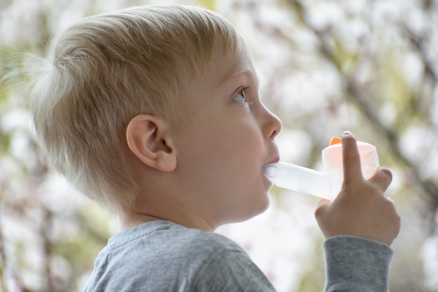 Un garçon blond fait une inhalation à la maison. arbres en fleurs