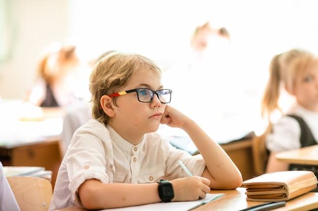 Garçon blond avec de grandes lunettes noires assis dans la classe, étudiant, souriant education à l'école primaire, premier jour d'école